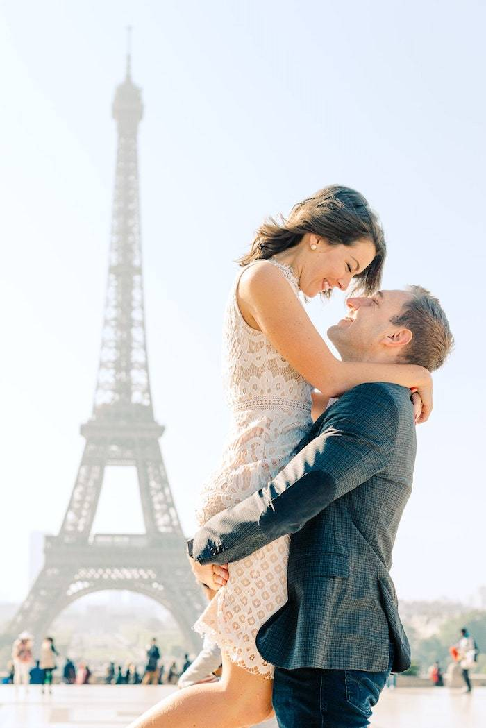 happy engaged couple in front of the eiffel tower in paris