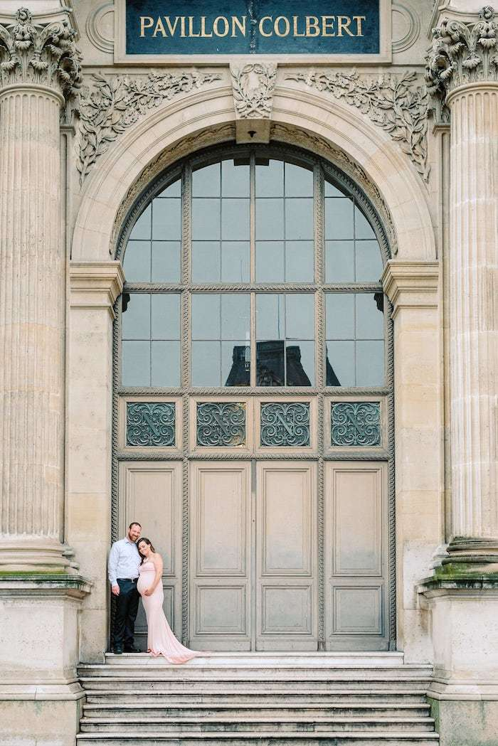 couple in front of louvre doors in paris during maternity photo session