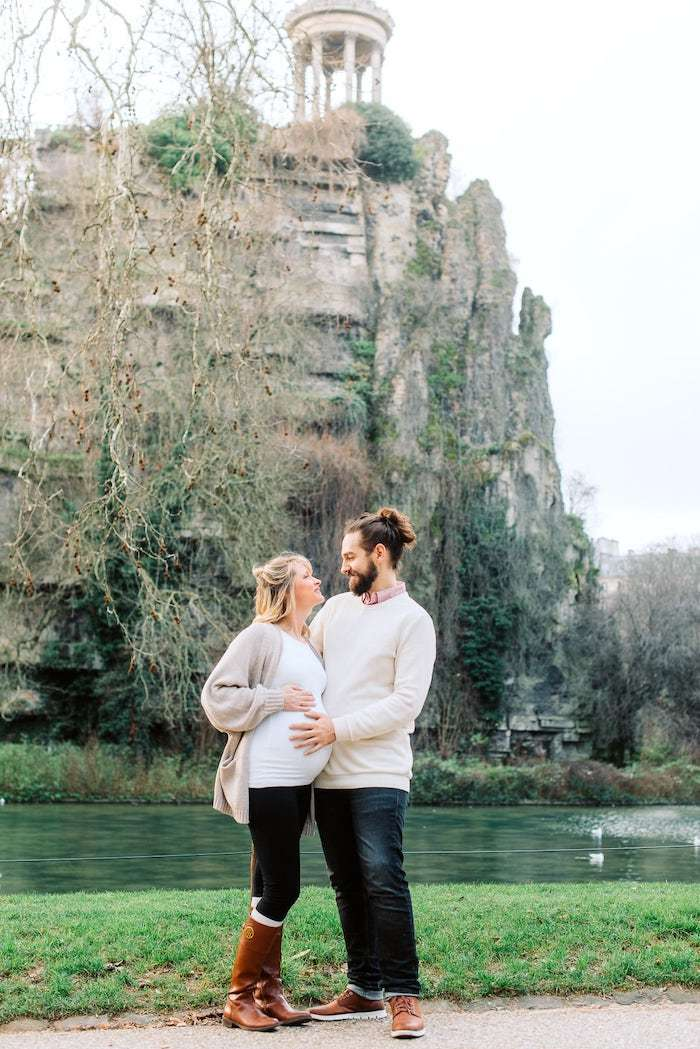 pregnant couple standing in front of buttes chaumont in paris