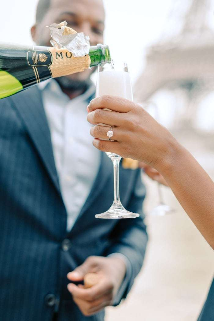 champagne after surprise proposal with engagement ring at the eiffel tower paris