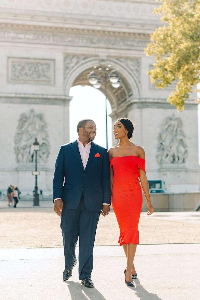 couple walking in front of the arc de triomphe paris