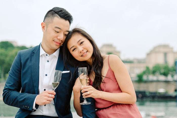 engaged couple with champagne in paris